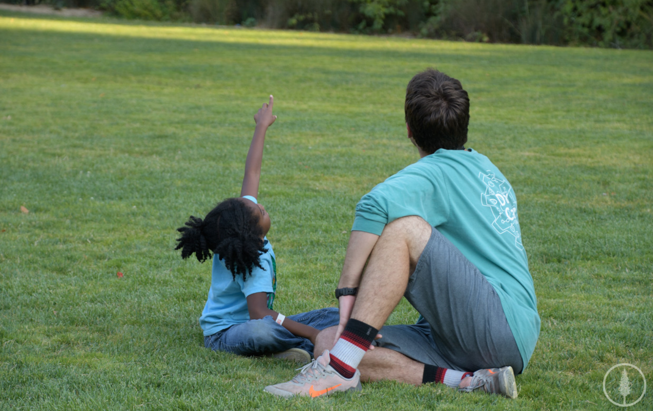 """A counselor wears his shirt as he plays """"I Spy"""" with one of the campers."""