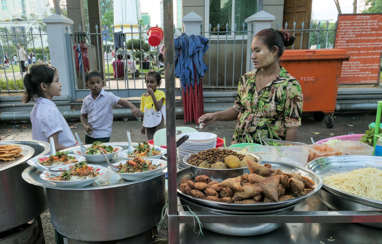 Family affair: The whole family come together at this samosa salad stall at the street food market by Maha Bandula Park, Yangon