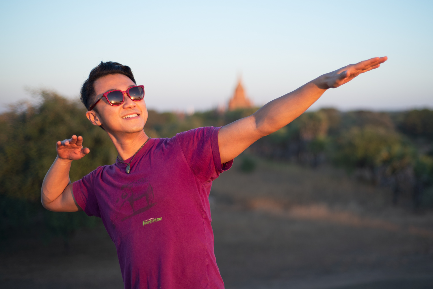 Matthew Seow signature pose in Bagan sunset with Dhammayan Gyi Temple in the background.