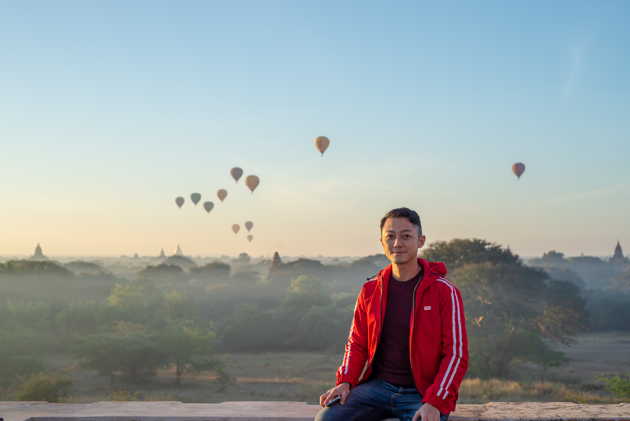 Portait with red jacket and hot air ballooons over Bagan after sunrise.