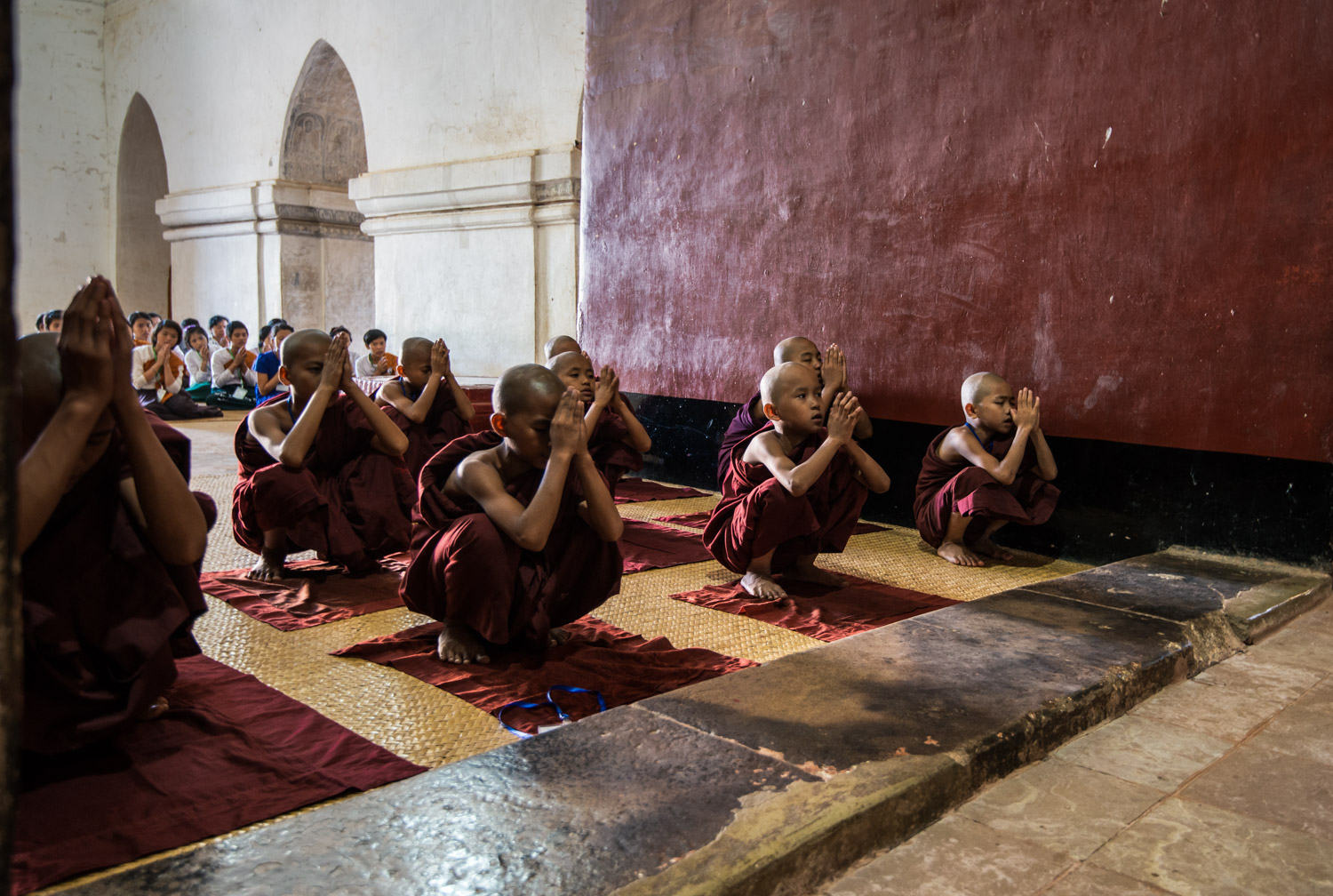 Novice Buddhist Monks in their saffron red robes squat and pray at the Ananda Phaya Temple in Bagan