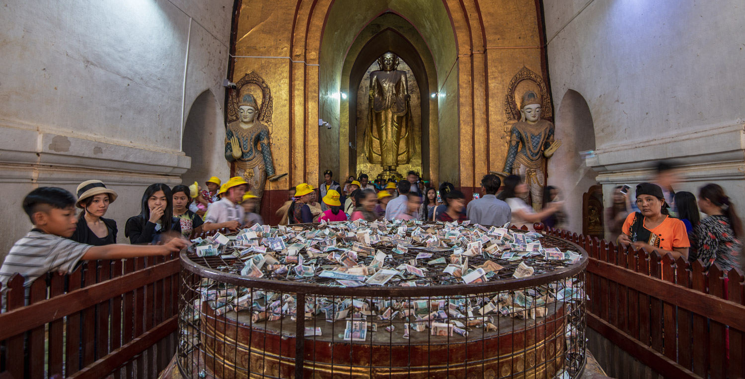 Offerings of money at the image of the Buddha's footprints at Ananda Phaya Temple in Bagan.