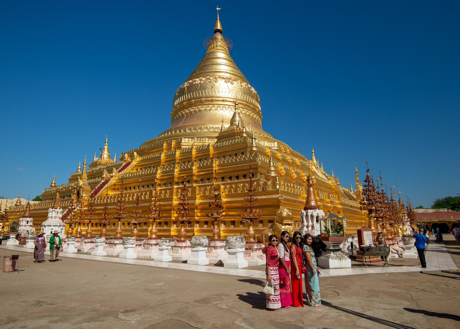 Girls pose in front of the Golden Shwezigon Pagoda in Bagan.
