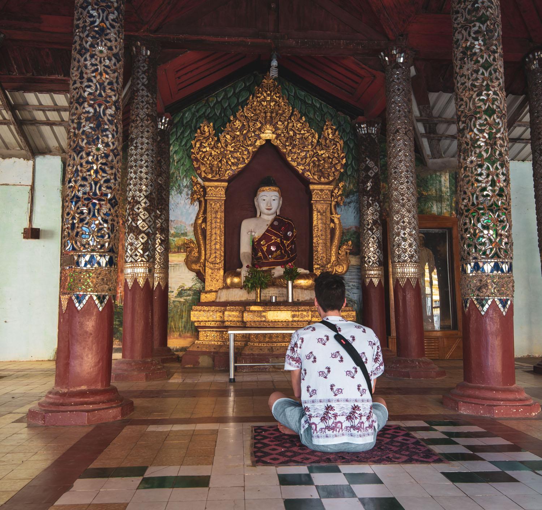 A tourist sits facing the Buddha in a pavilion at Shwezigon Pagoda in Bagan.