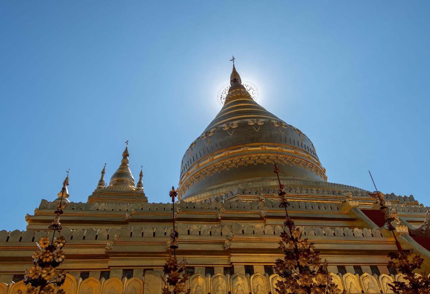 Shwezigon Pagoda's stupa is backlit by the midday sun.