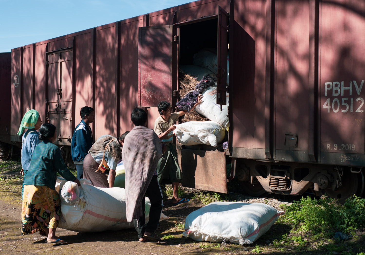 Unloading bags of straw from the Mandalay-Lashio train.
