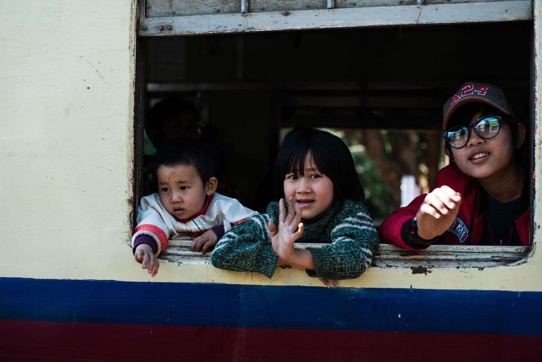 Children waving from the window of the Mandalay-Lashio train