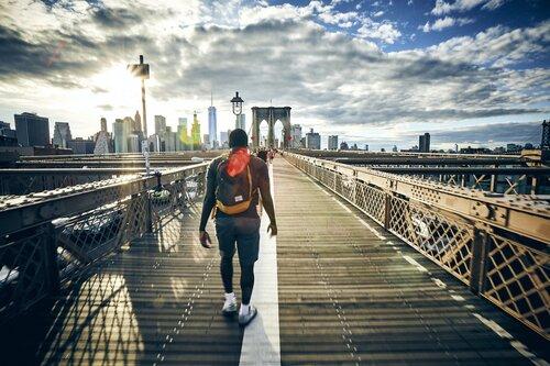 Man wearing backpack crossing the Brooklyn Bridge