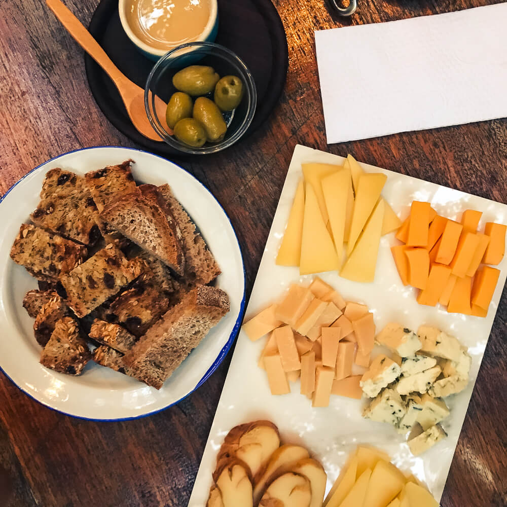 A cheese plate with bread and olives