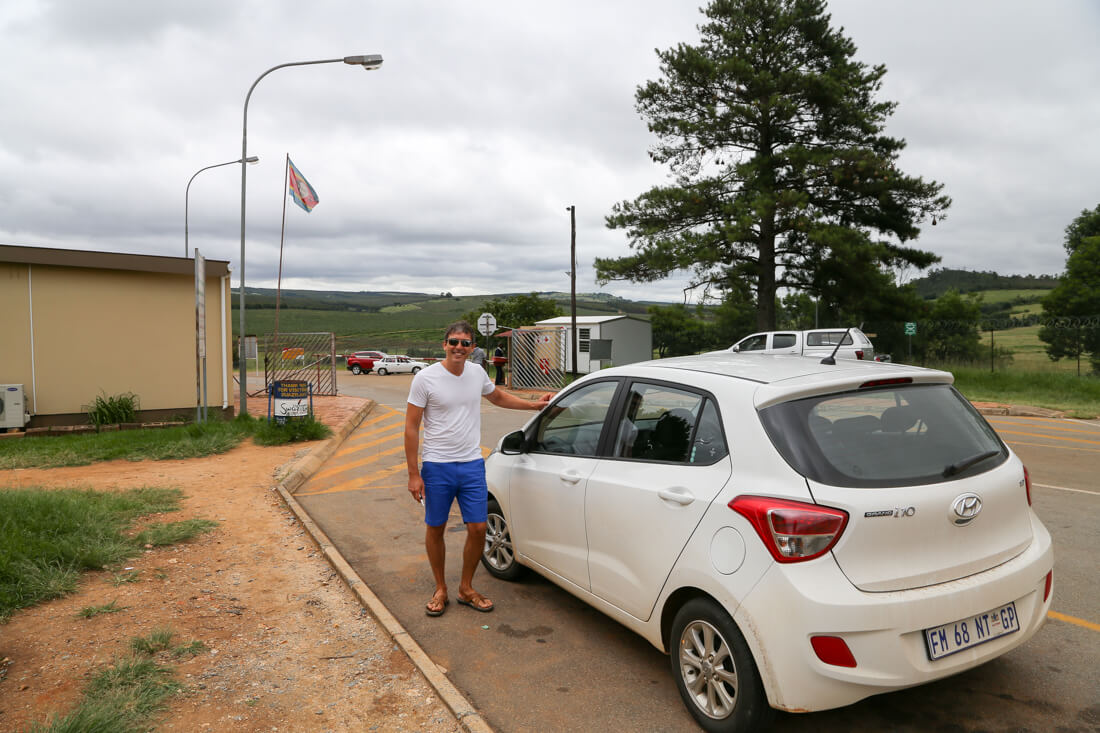a man standing outside a small white car in Swaziland
