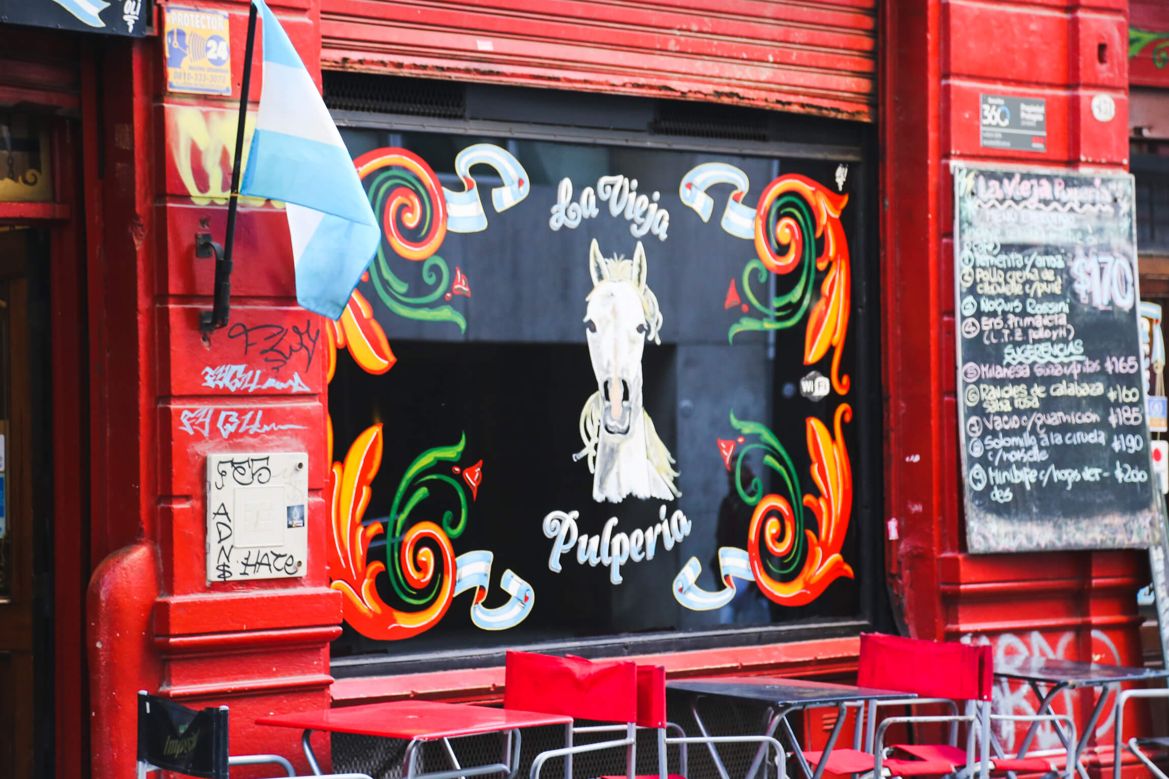 Visit Buenos Aires to see this red restaurant facade decorated with Argentine fileteado paint