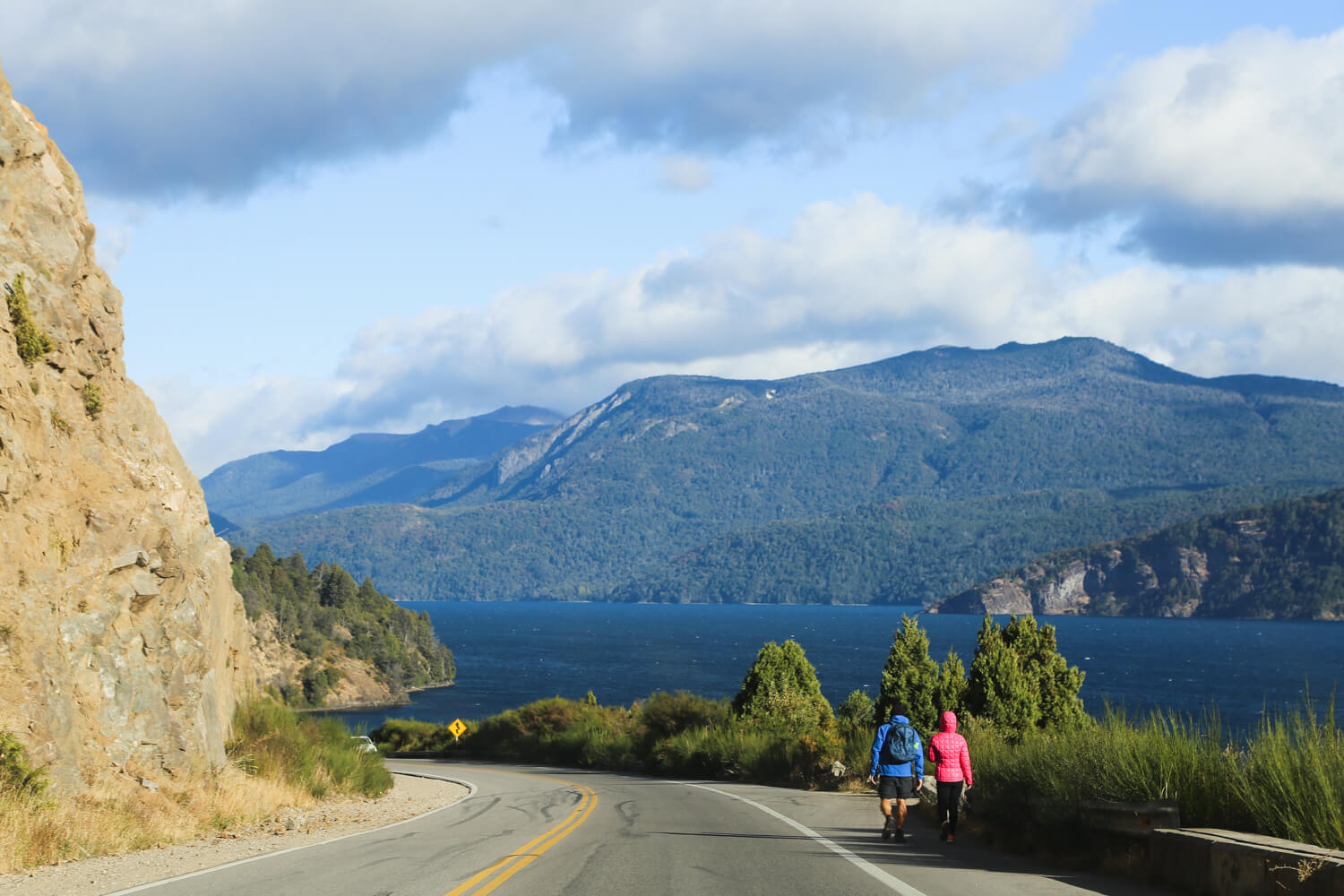 Two hikers walk alongside a highway by a lake with mountains in the background on the Ruta de los Siete Lagos drive in Patagonia