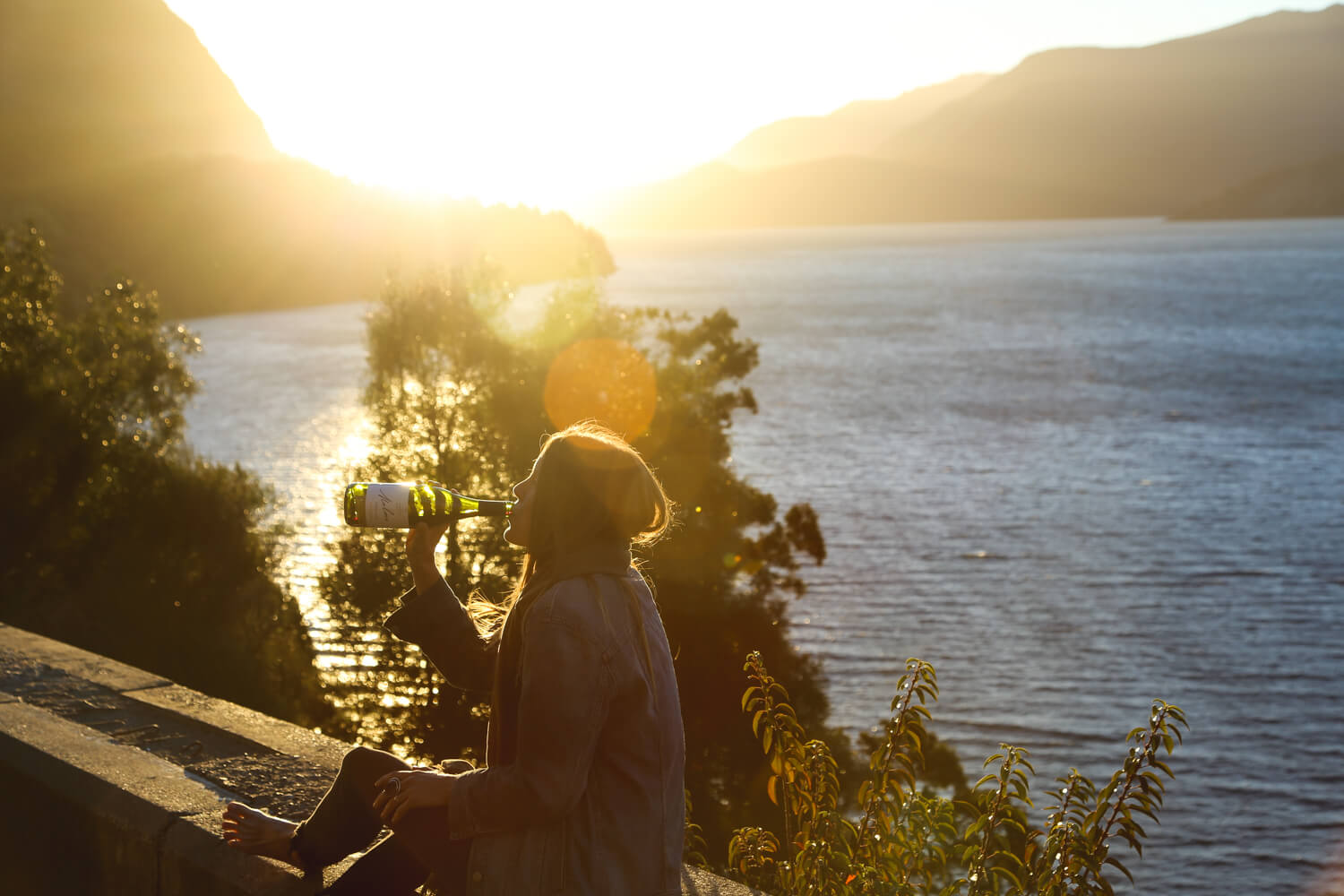 A woman drinks from a bottle of wine in front of a lake with the sun setting behind her on the Ruta de los 7 Lagos Patagonia