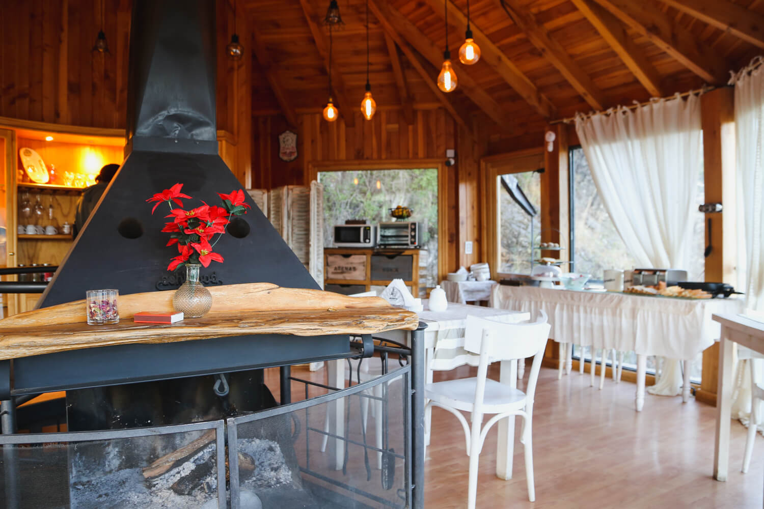 A fireplace and tables and chairs inside a wooden room at the best hotel in San Martin de los Andes Argentina