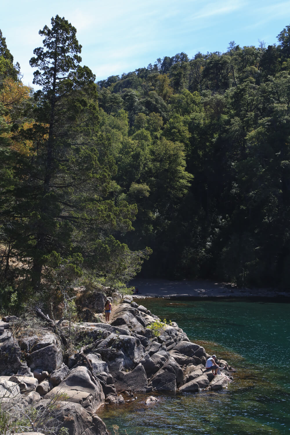 Boulders jut out into the lake with a beach in the background in San martin de los Andes Patagonia