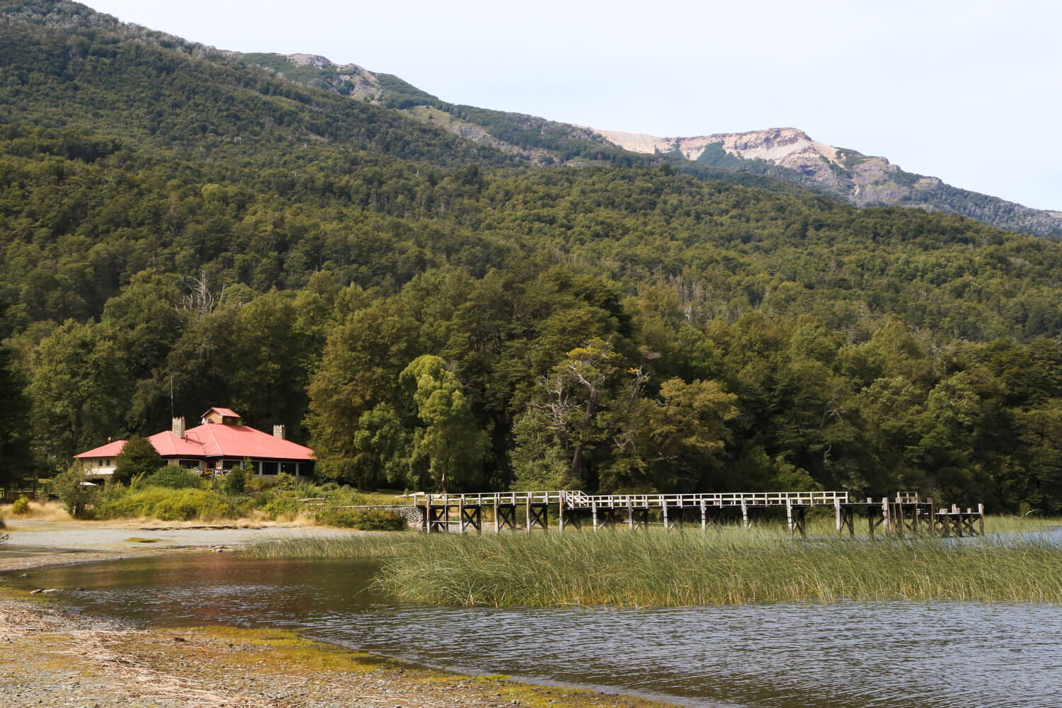 A beach with a wooden pier over the water in san martin de los andes argentina