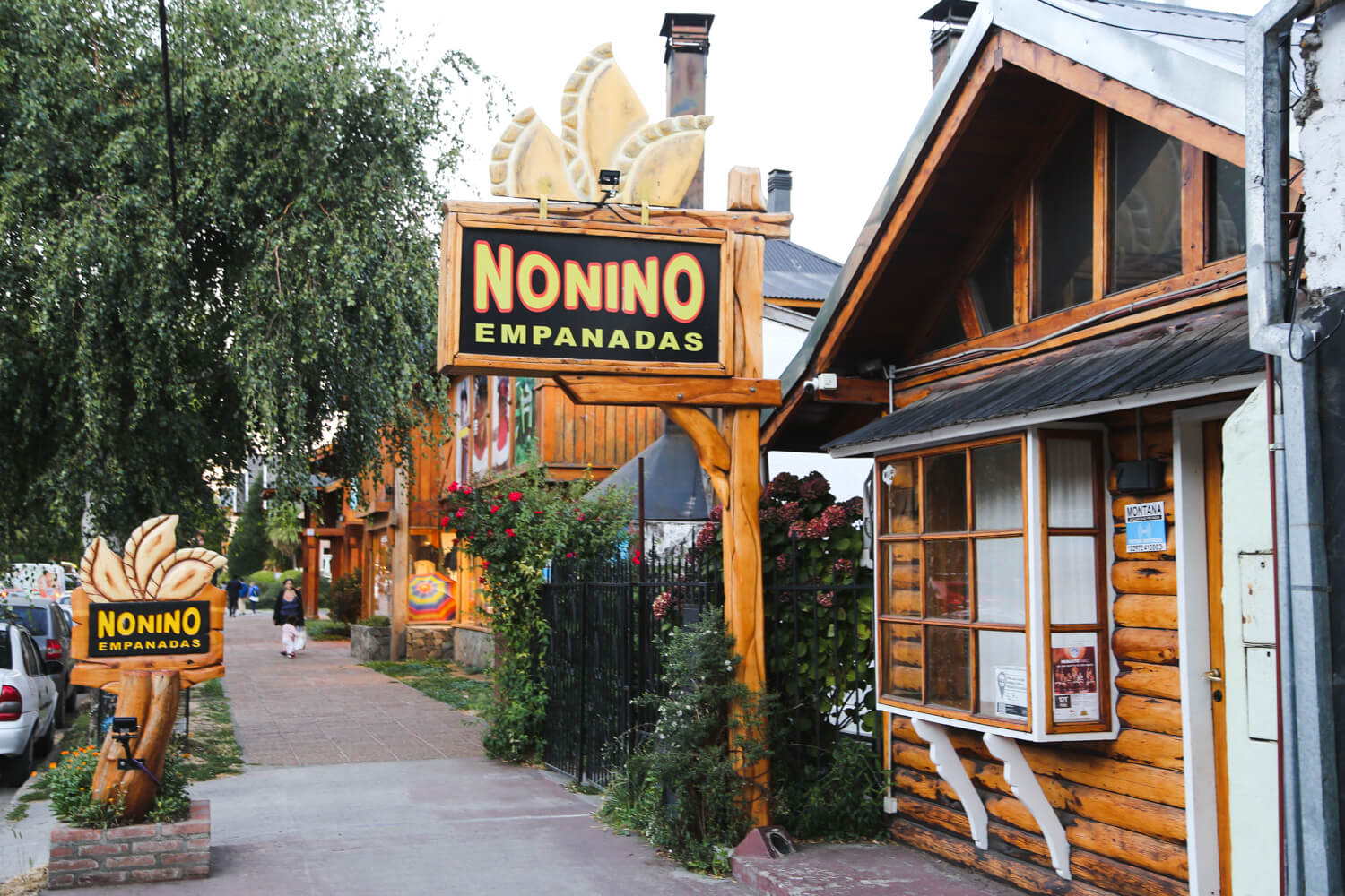 A restaurant in a log cabin is next to a sidewalk in downtown san martin de los andes argentina
