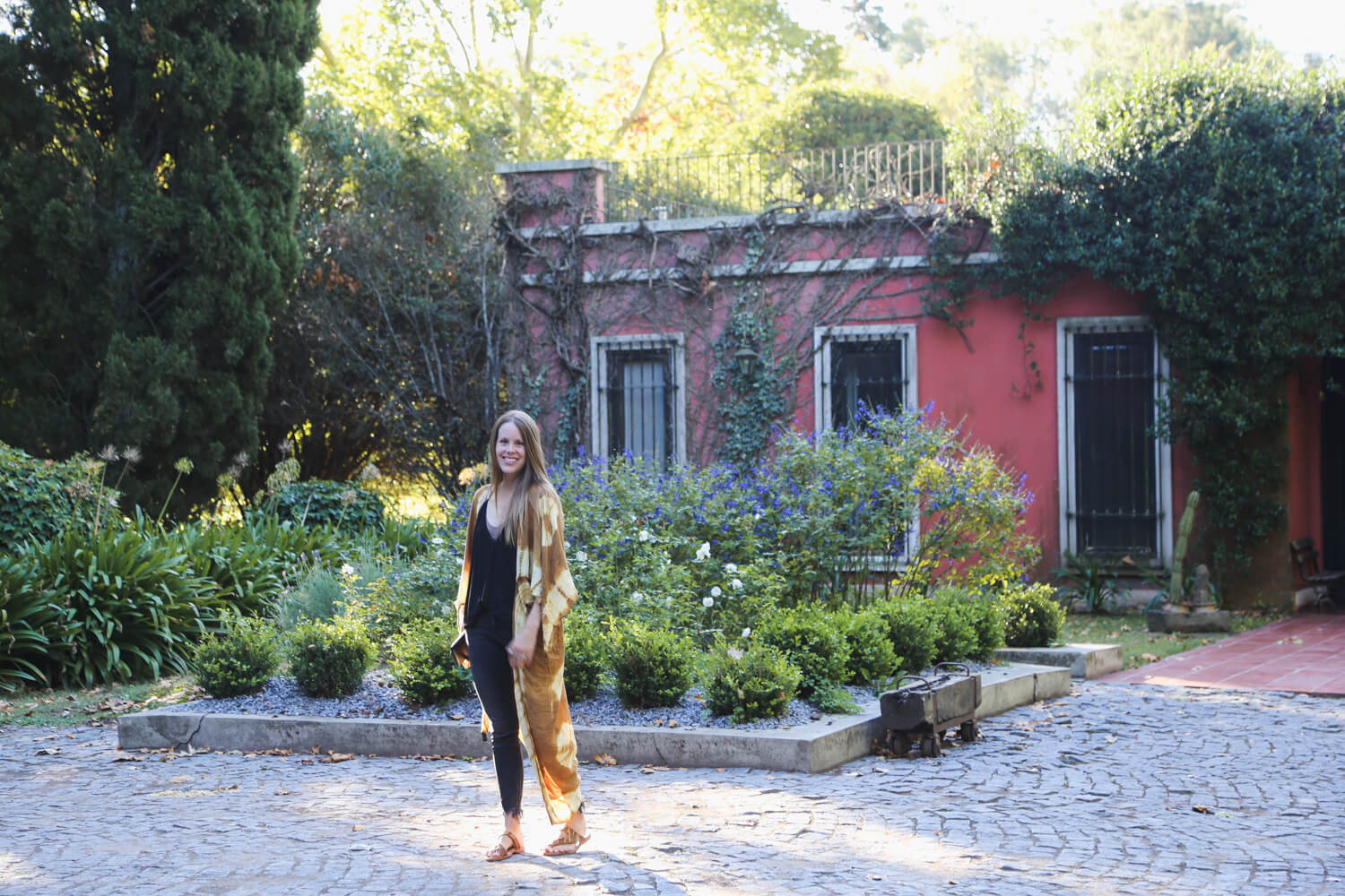 A woman stands in front of a garden and a terracotta colored mansion in Buenos Aires