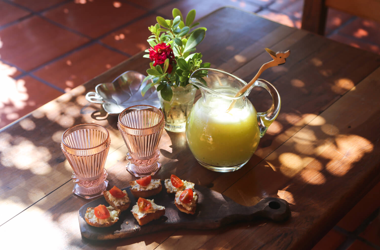 A pitcher of lemonade and a platter of bruscetta on a wooden table at Estancia la Banada San Miguel del Monte