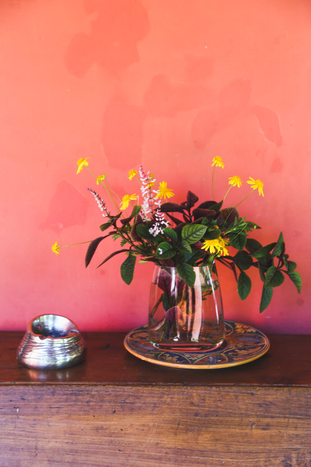 Flowers in a vase in front of a red wall at Estancia la Bandada Argentina