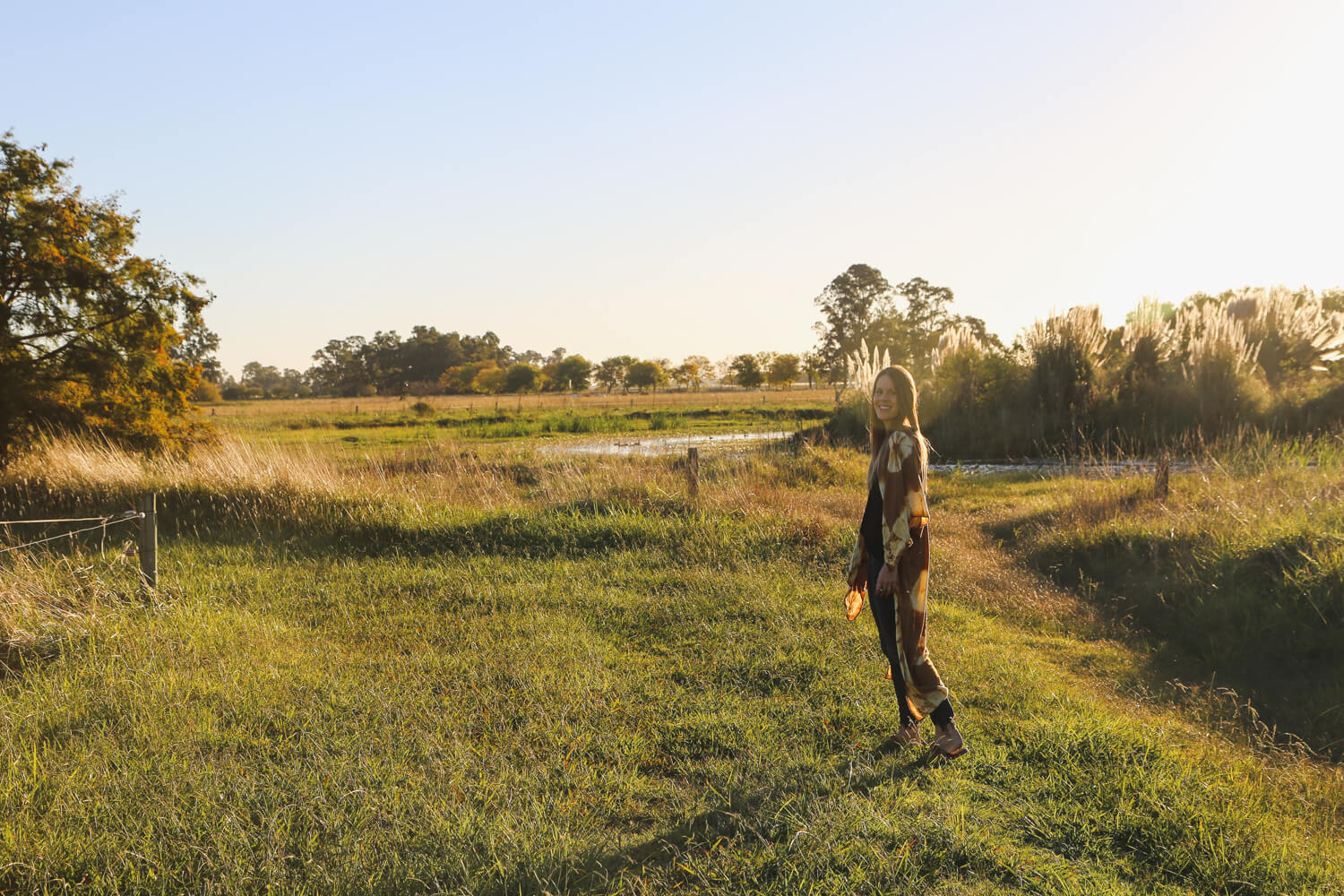 A woman walks in the pasture at Estancia La Bandada during sunset