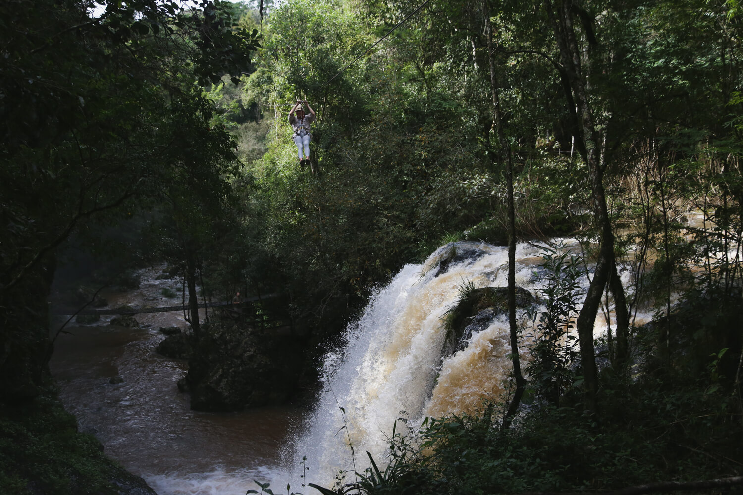 A woman zip lining over a waterfall in the Argentine jungle on a northeast Argentina road trip