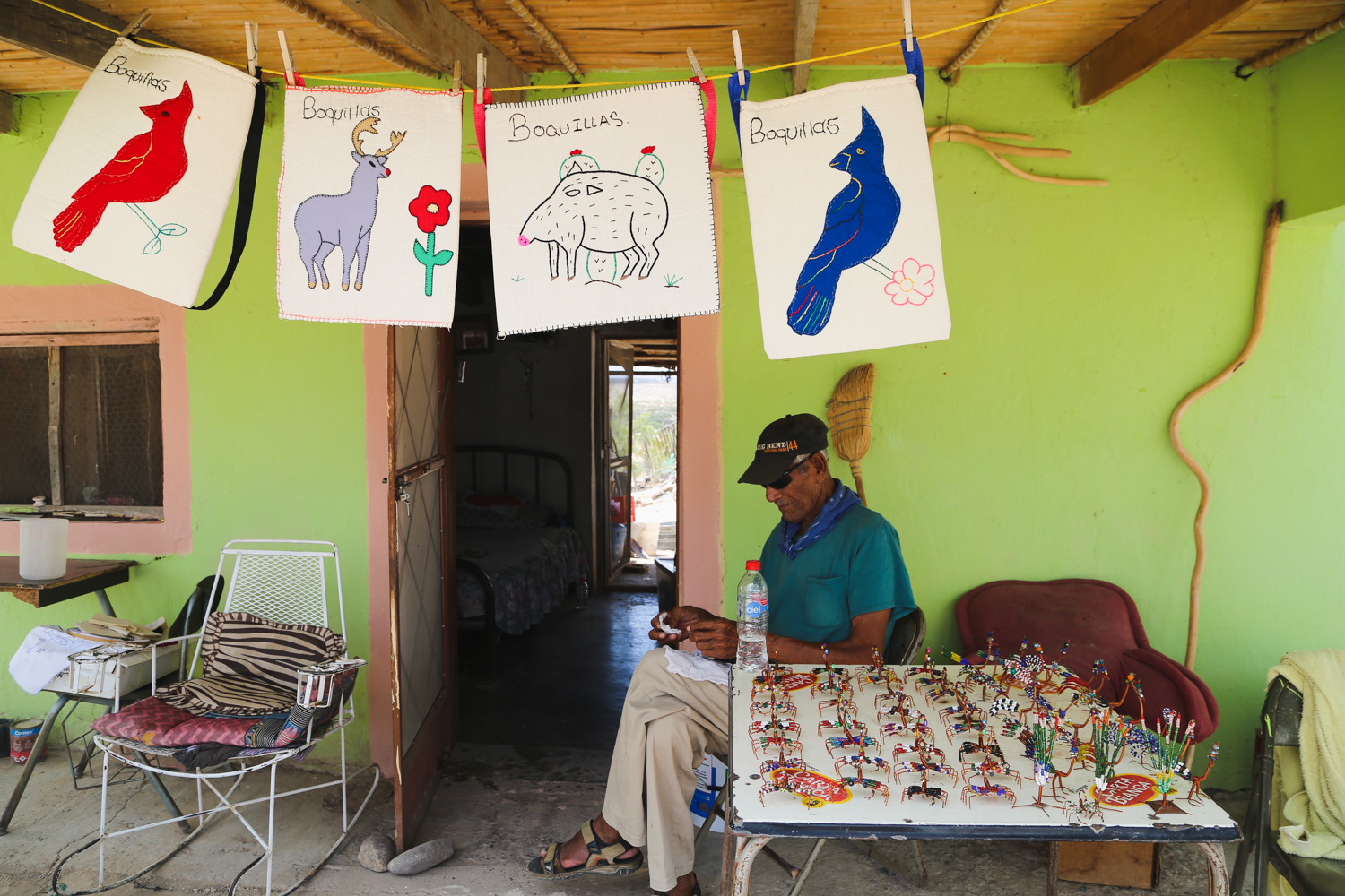 An older man is sitting on a chair on a front porch in front of a table filled with knick knacks for sale in Boquillas Mexico