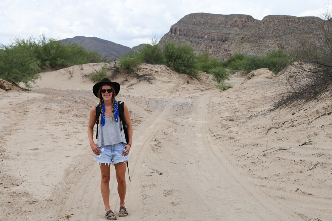 A woman stands in the sandy road in front of a mountain in Boquillas Mexico