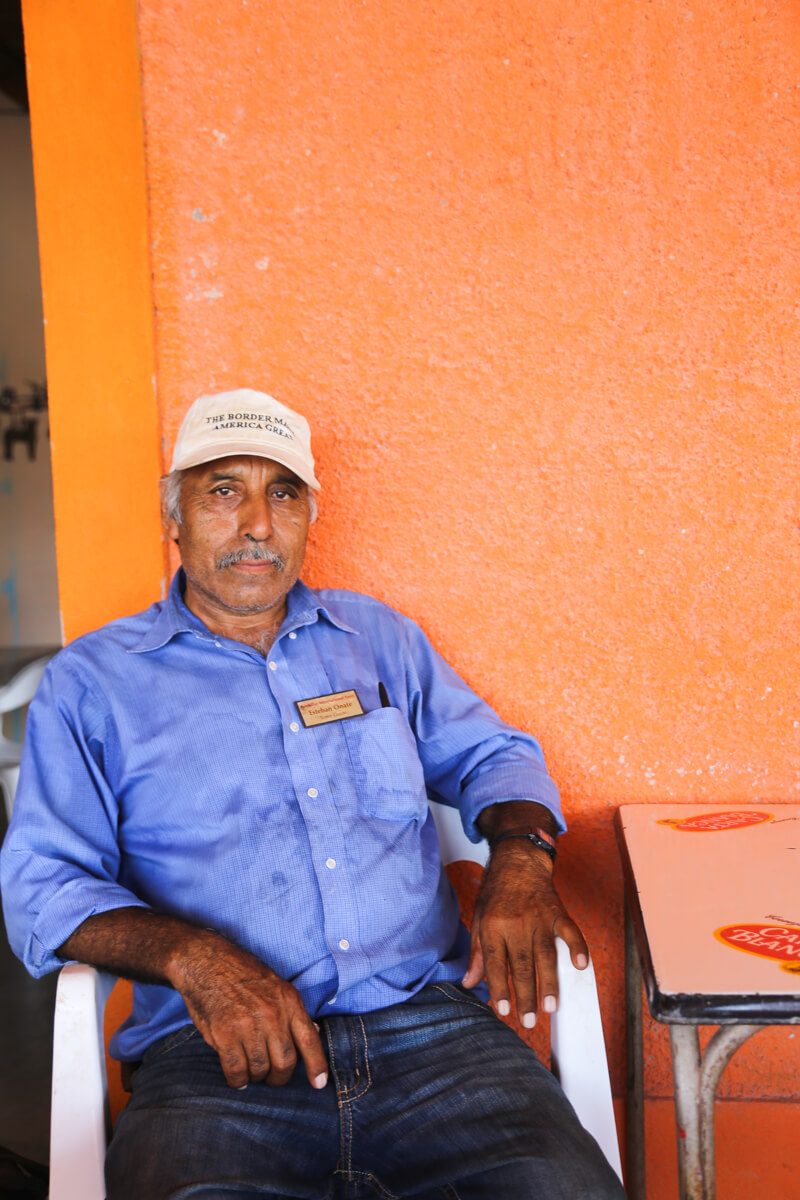 A man sits on a lawn chair in front of an orange wall in Boquillas del Carmen Mexico