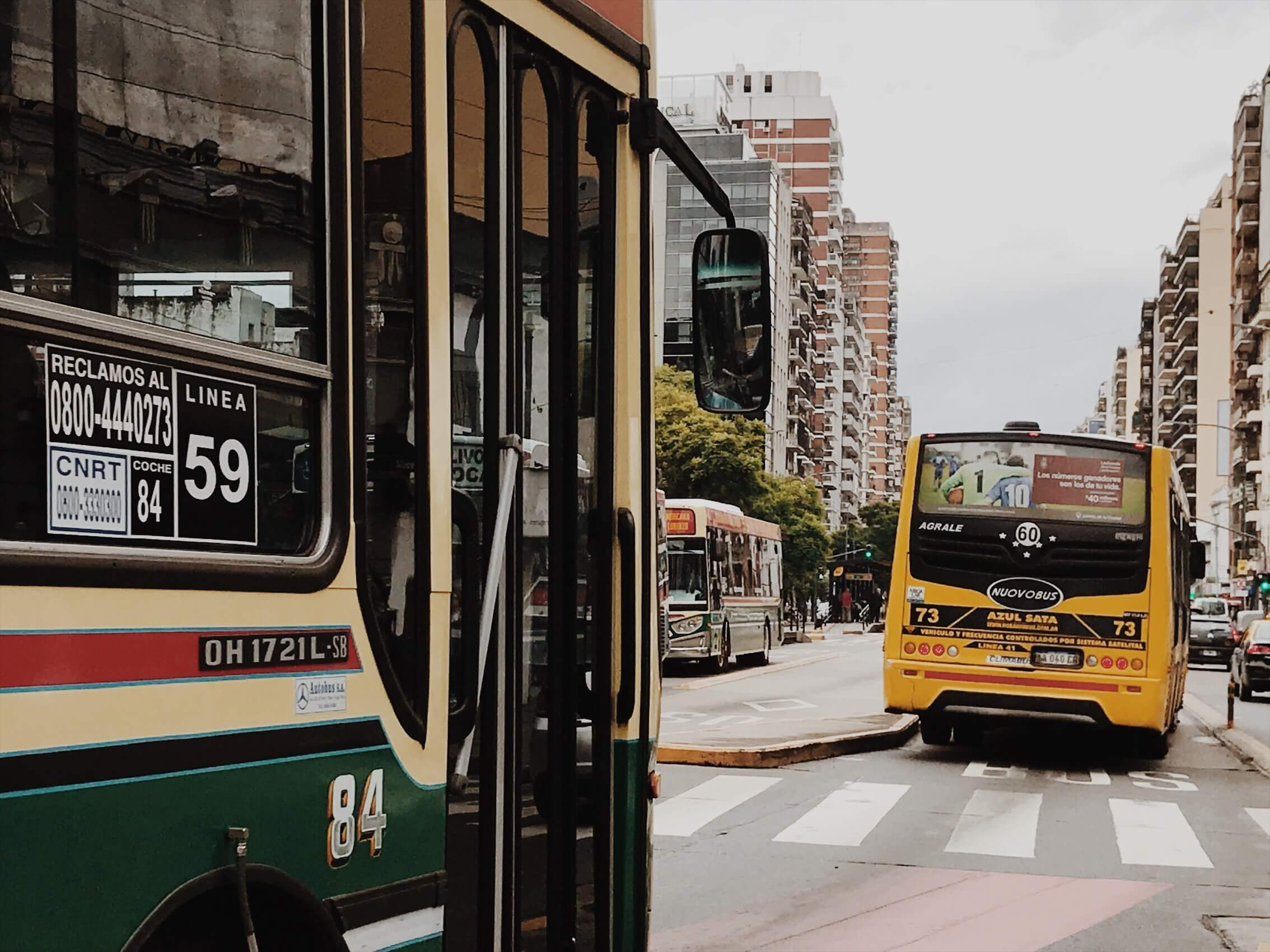 City buses wind down a avenue lined by tall apartment towers form a large part of Buenos Aires public transportation