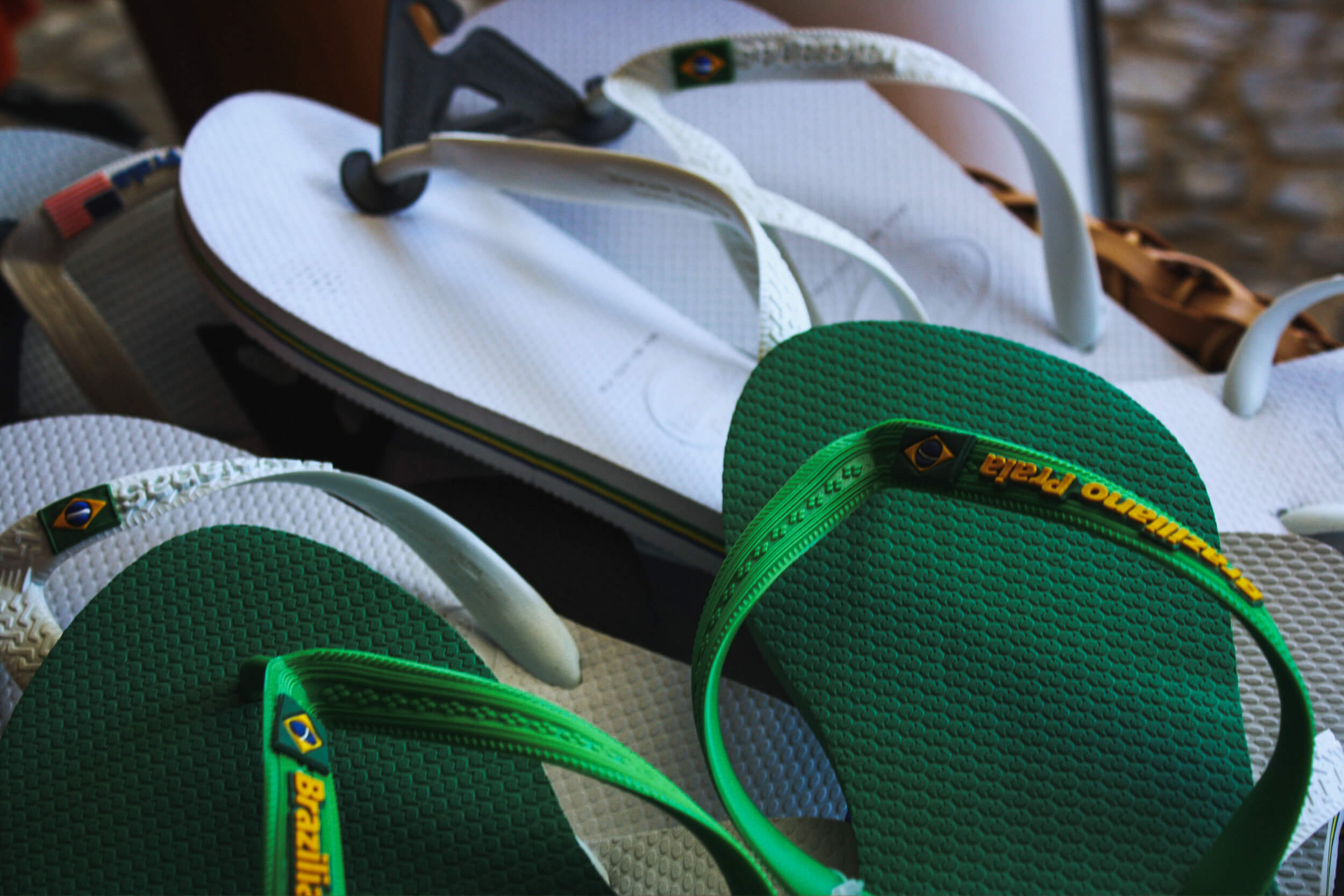 A basket filled with green and white flip flops, cute walking shoes for women, sits on the sidewalk.