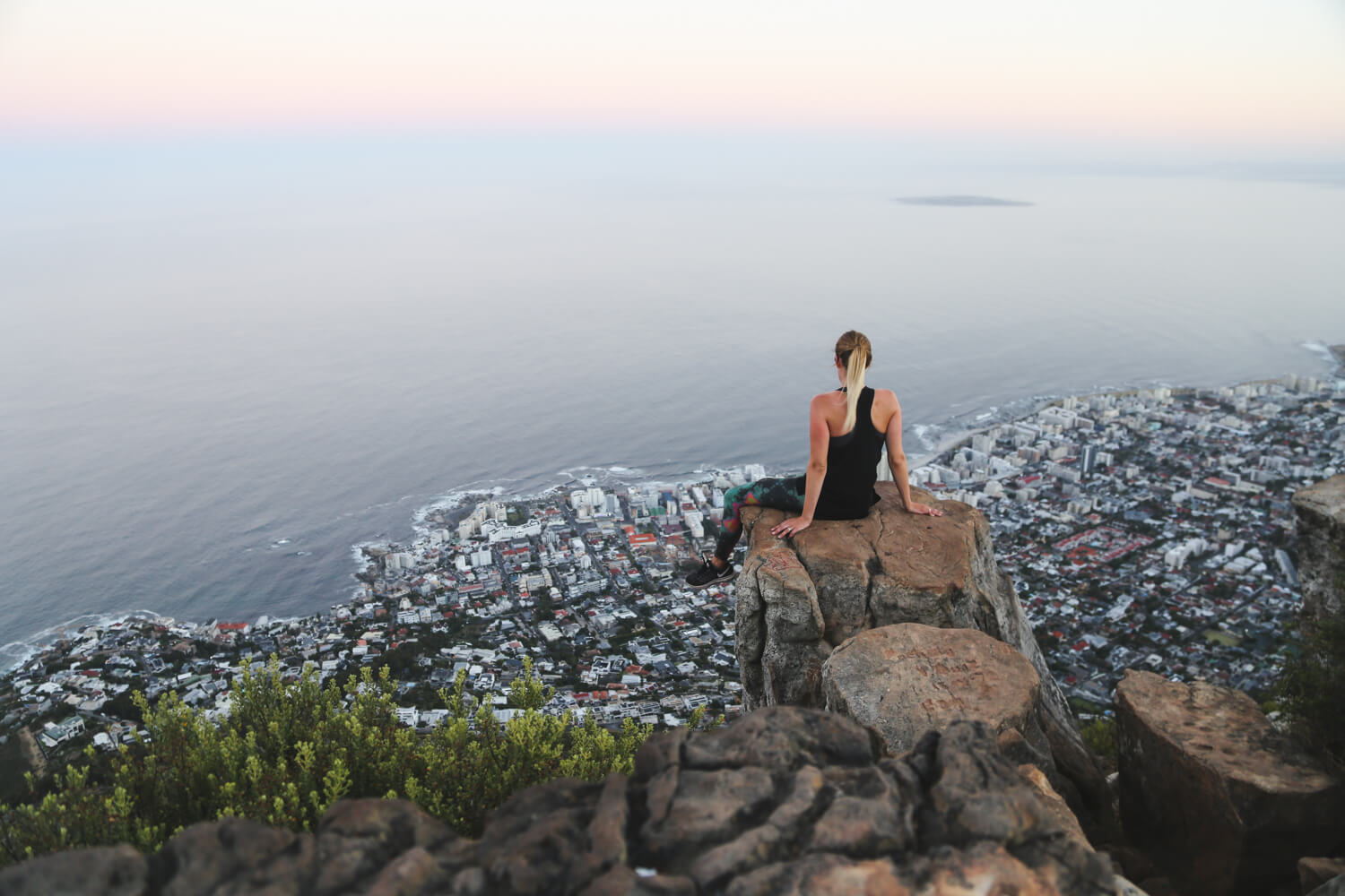 A woman sits on a rock on a cliff overlooking Cape Town below
