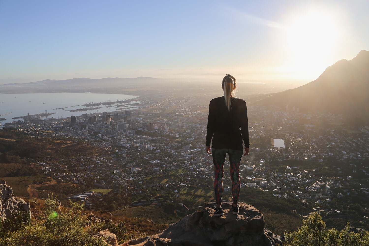 A woman in athletic clothes from a South Africa packing list stands on top of Lion's Head overlooking Cape Town below