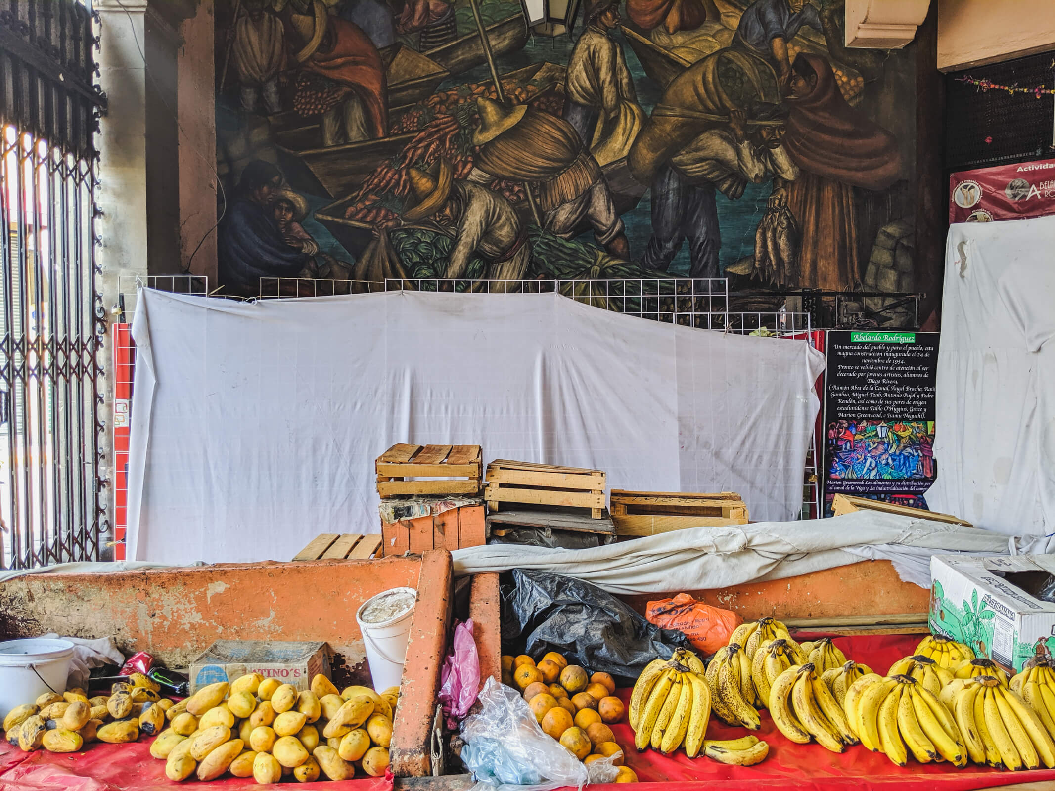 A table in a market is filled with mangos, oranges, and bananas in Mexico City