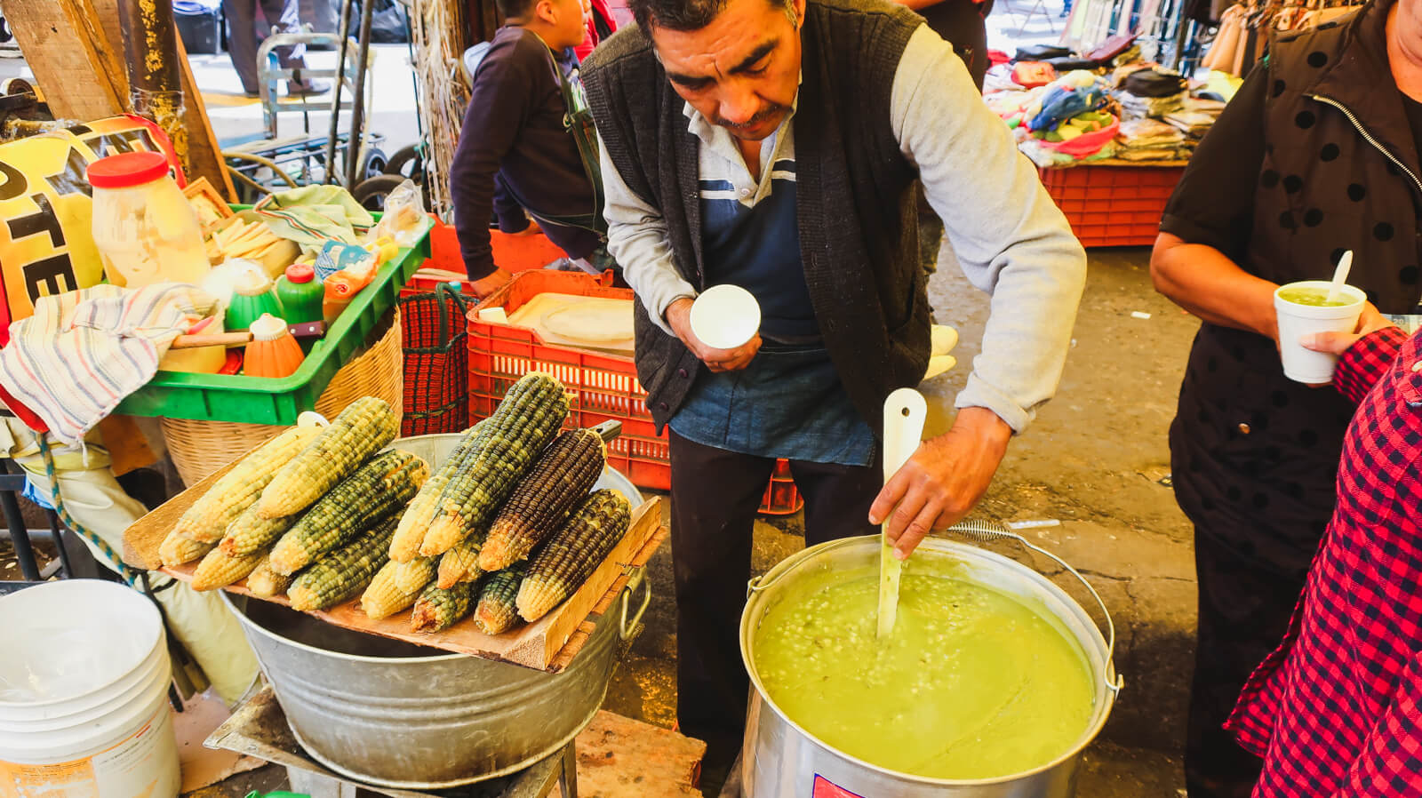 A man in a Mexico City market is standing behind a small table filled with blue corn on the cob and stirs a pot of corn