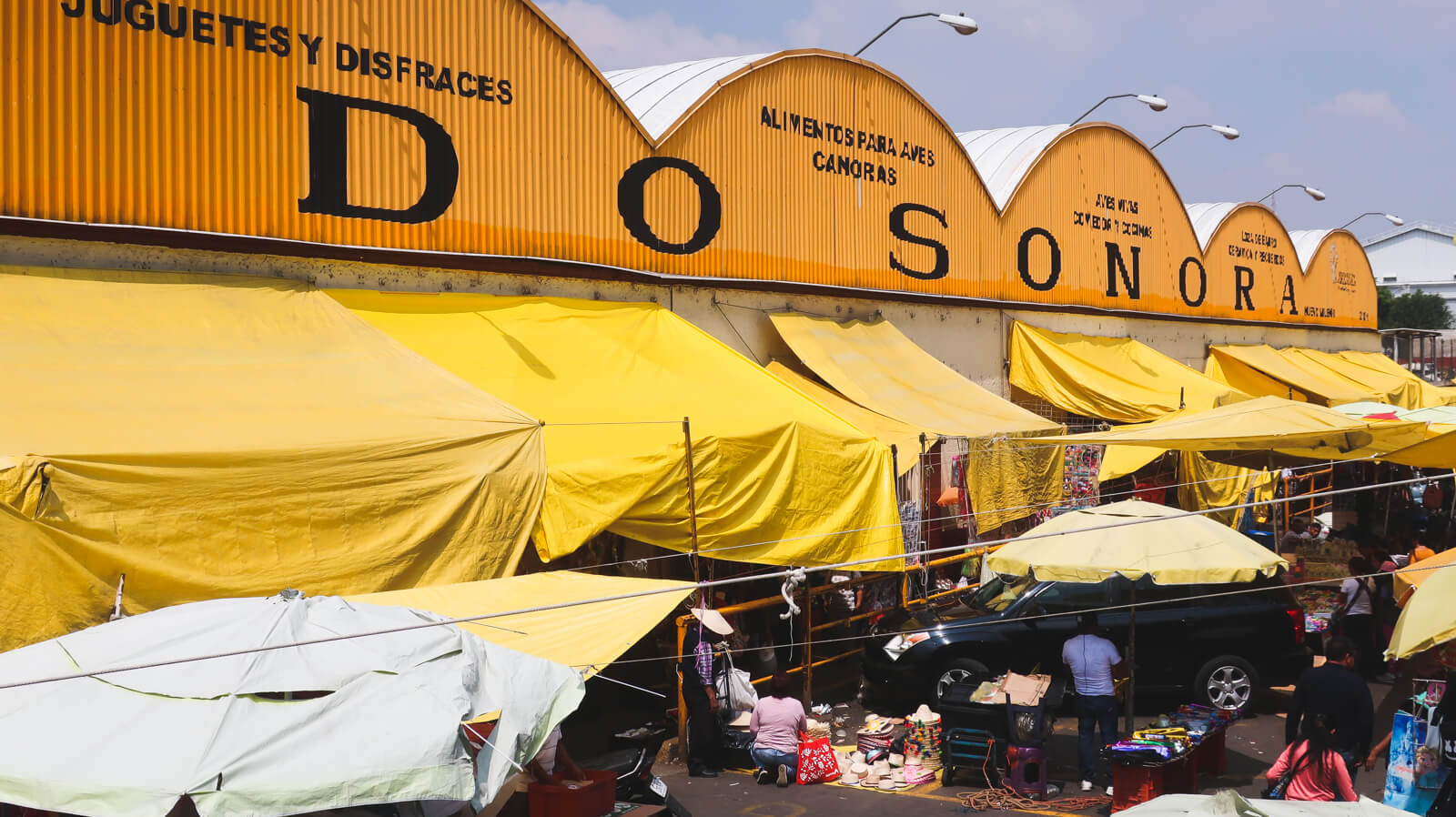 The yellow Sonora Market exterior with a group of yellow tents in front on a market tour in Mexico City