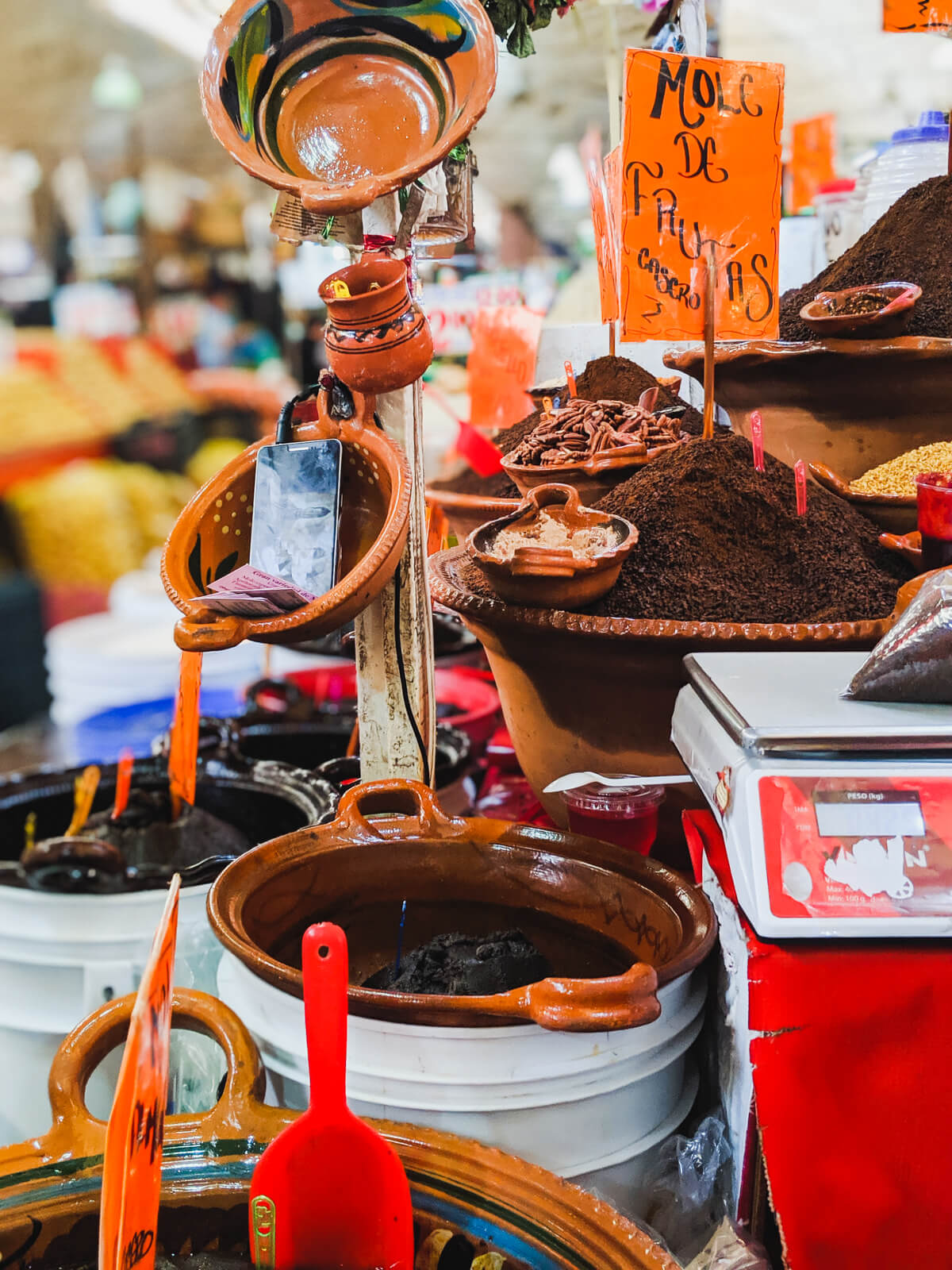 Large jars of mole and spices sit in a Mexico City market