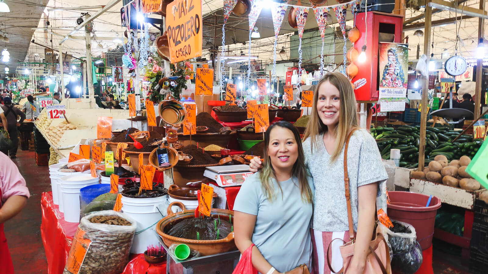 Two women stand in front of a stand selling spices in a Mexico City market