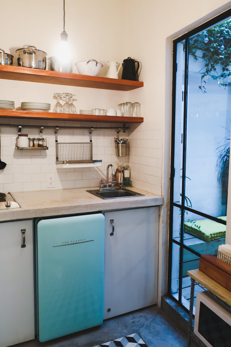 A turquoise mini fridge sits under a concrete counter top in a small kitchen in the perfect Airbnb for Mexico City in 3 days