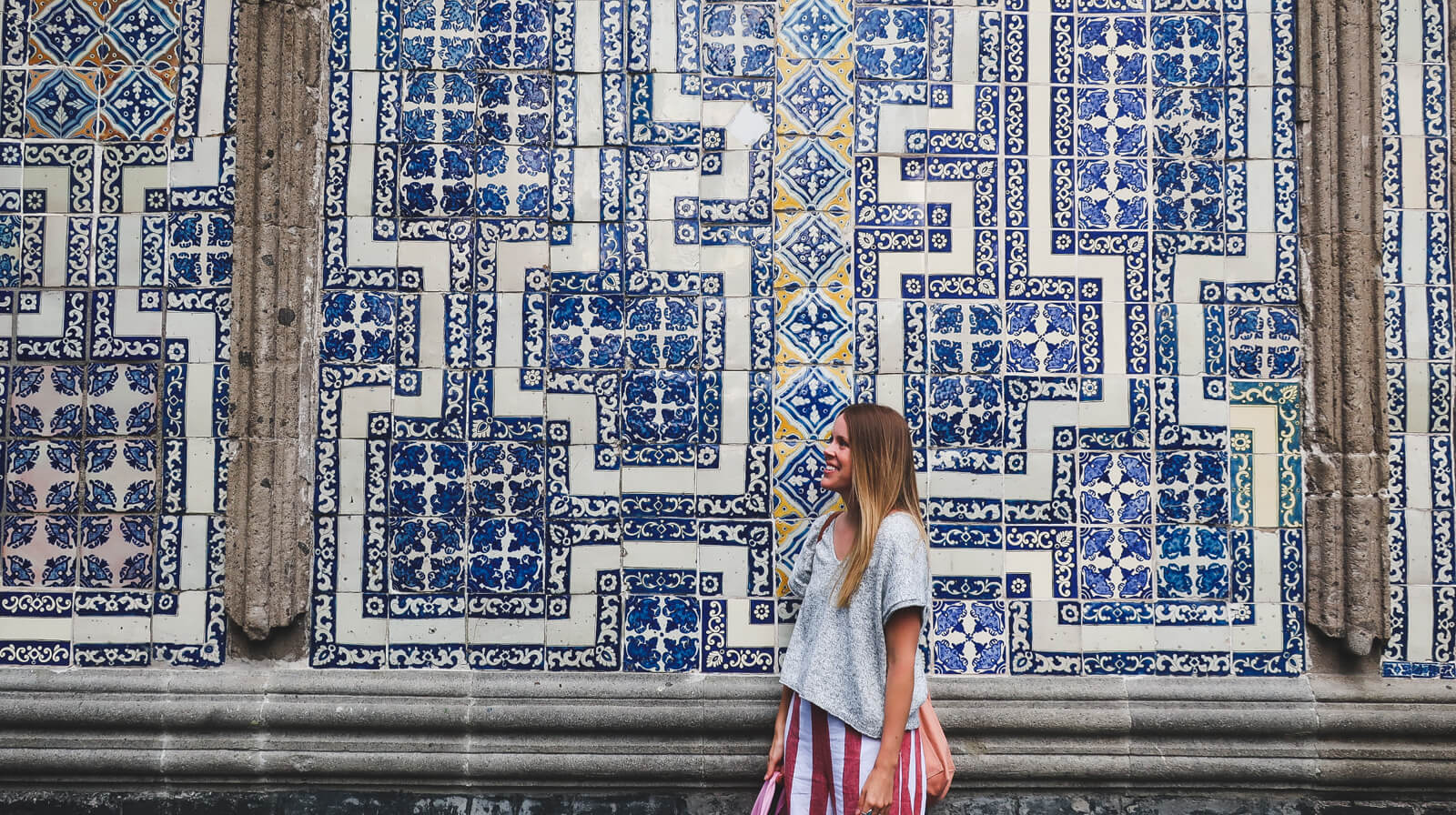 A woman stands in front of a blue tiles wall while exploring Mexico City in 3 days