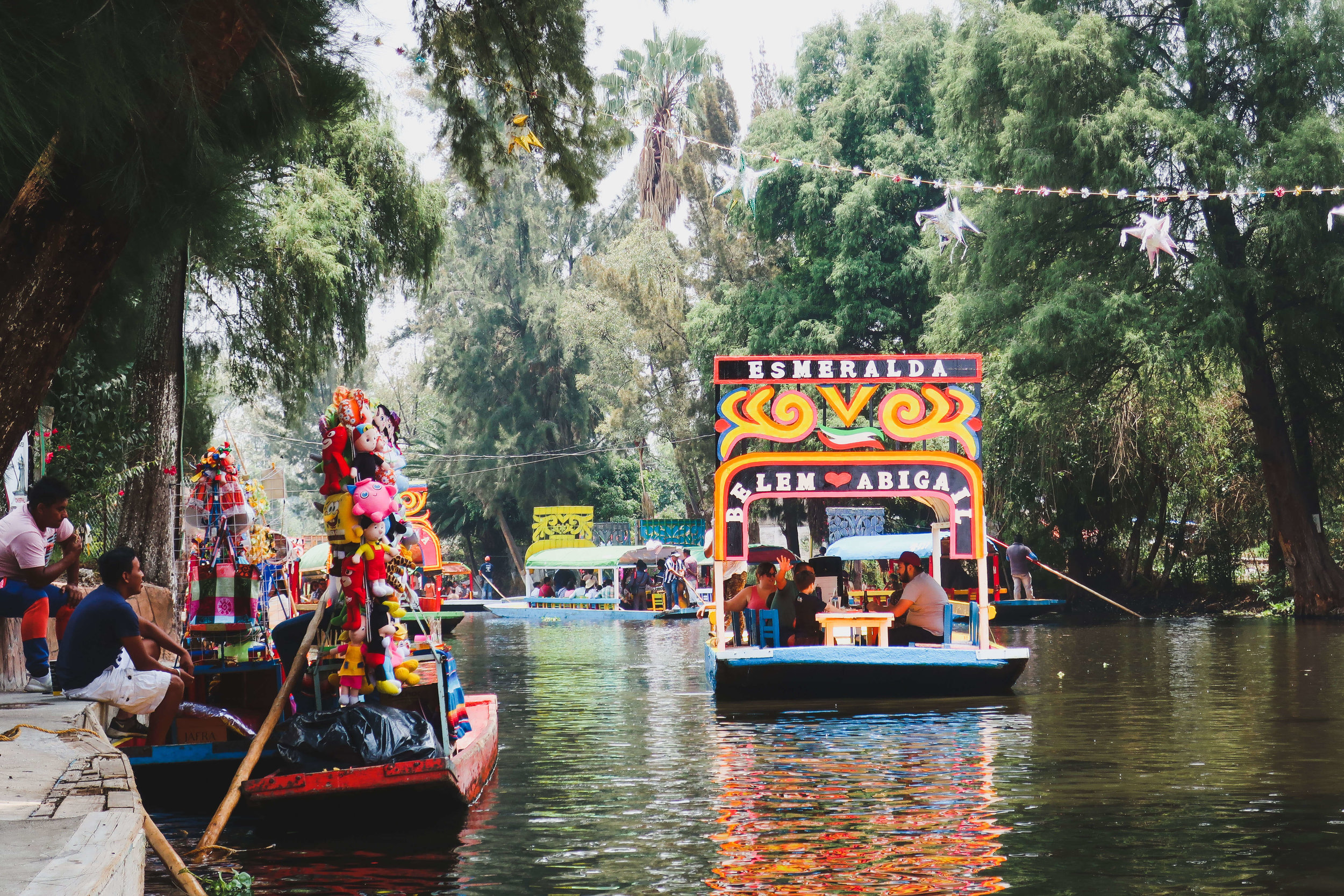 A colorful boat rows through the canals of Xochmilco on a Mexico City weekend afternoon