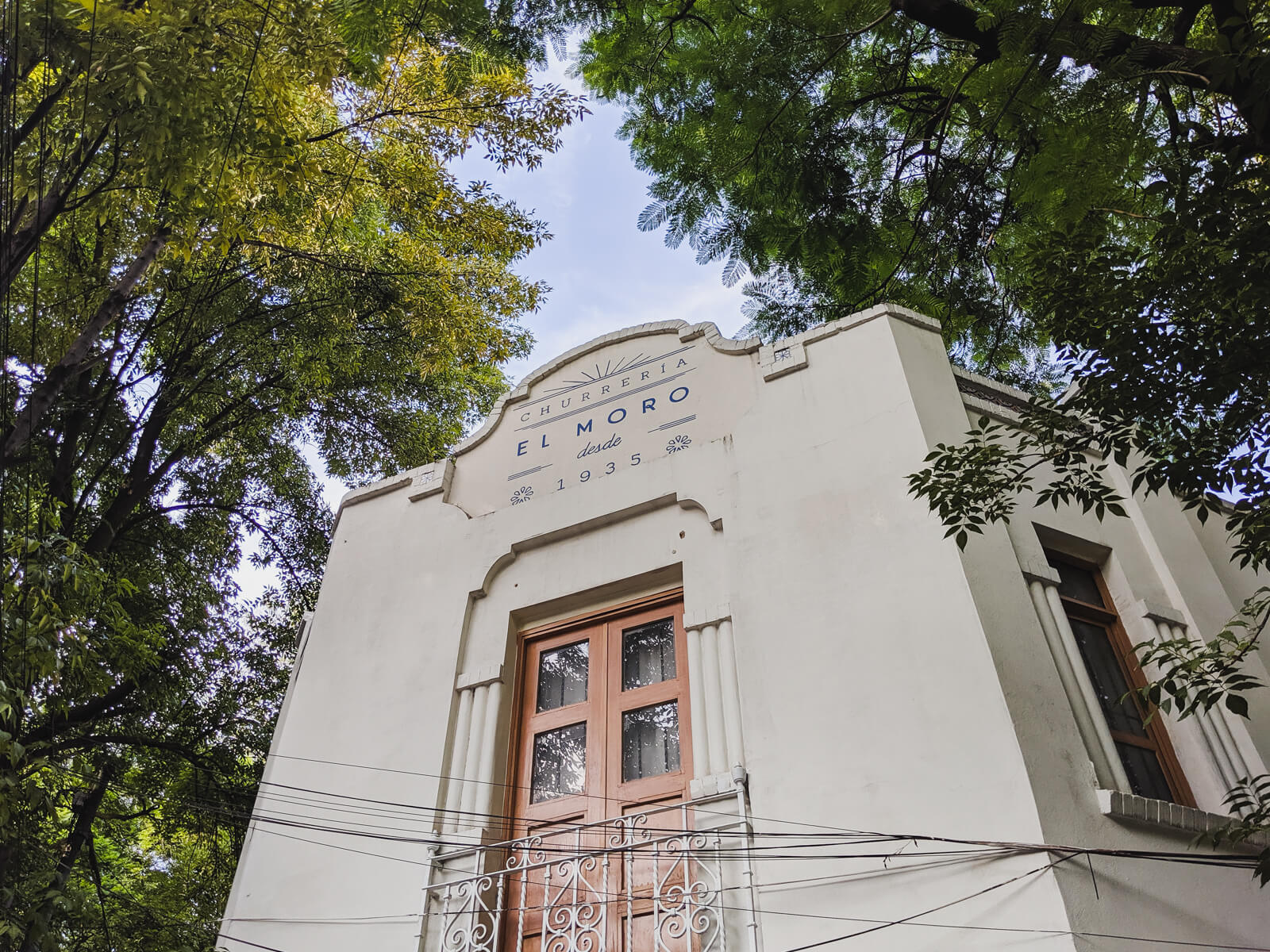 An art deco building stands on a street corner below a canopy of trees in Mexico City