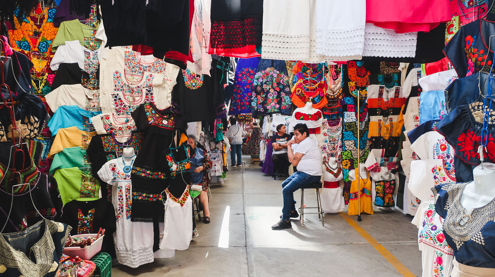 Colorful traditional clothing hang from stalls in the artisan market in Mexico City
