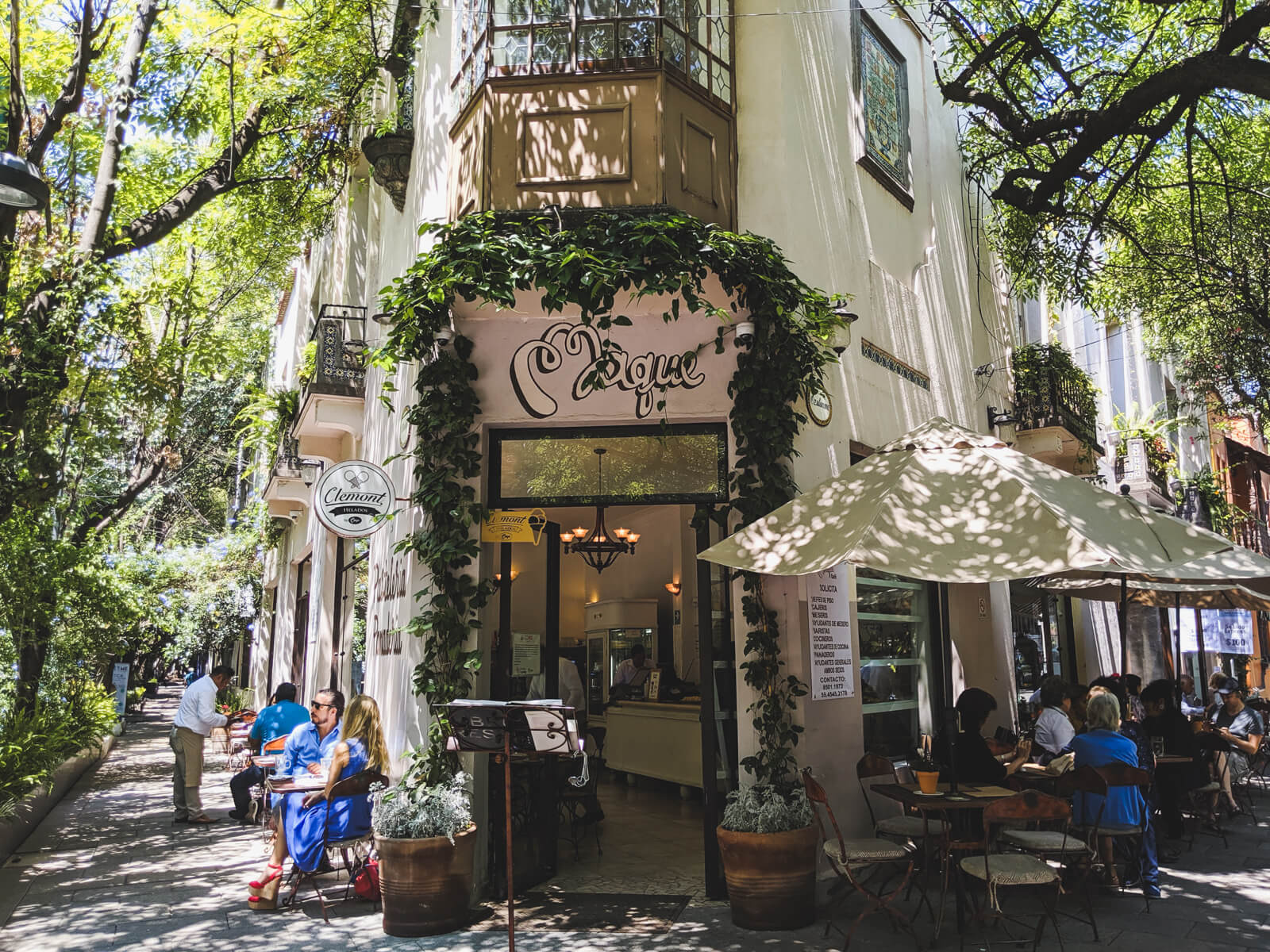 A coffee shop stands on a tree lined street corner in Mexico City