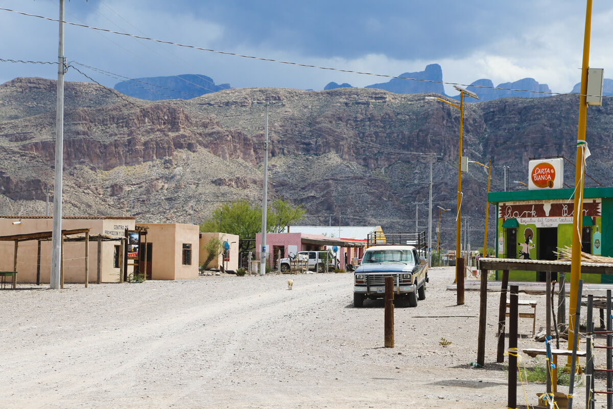 A truck is parked on a dirt road in a small Mexican village with a mountain range in the background