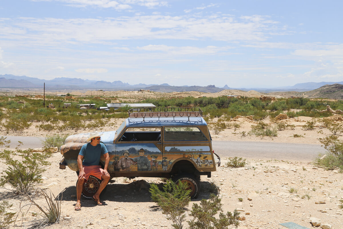 A man sits on the tire of an antique car in the middle of the desert in the Terlingua ghost town