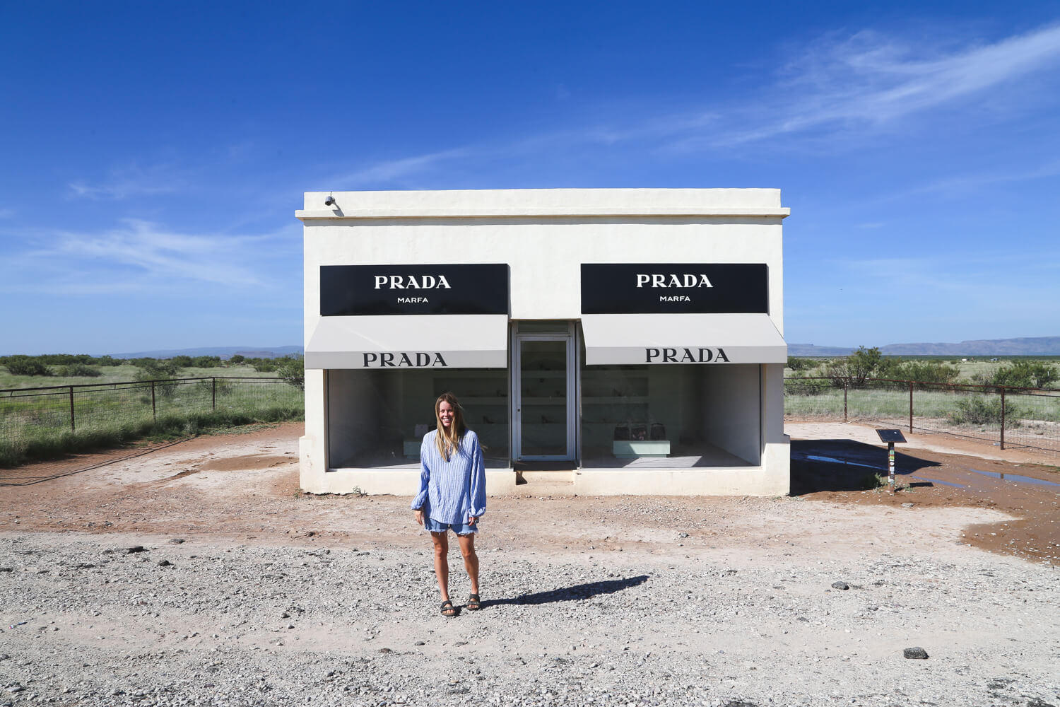 A woman does a handstand against a Prada storefront in the middle of the West Texas desert
