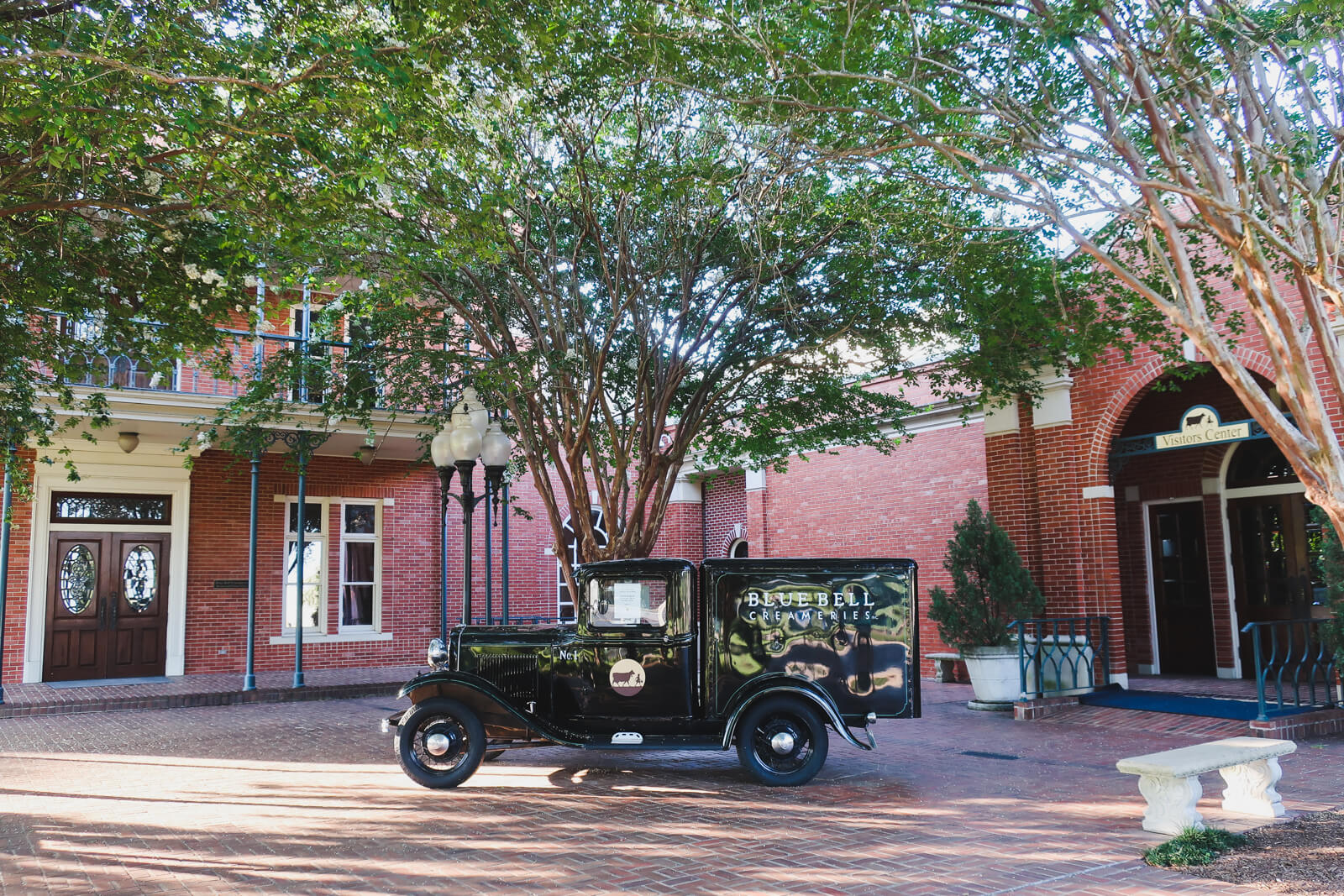 An antique car sits on a brick patio in front of the Blue Bell Factory in Brenham Texas