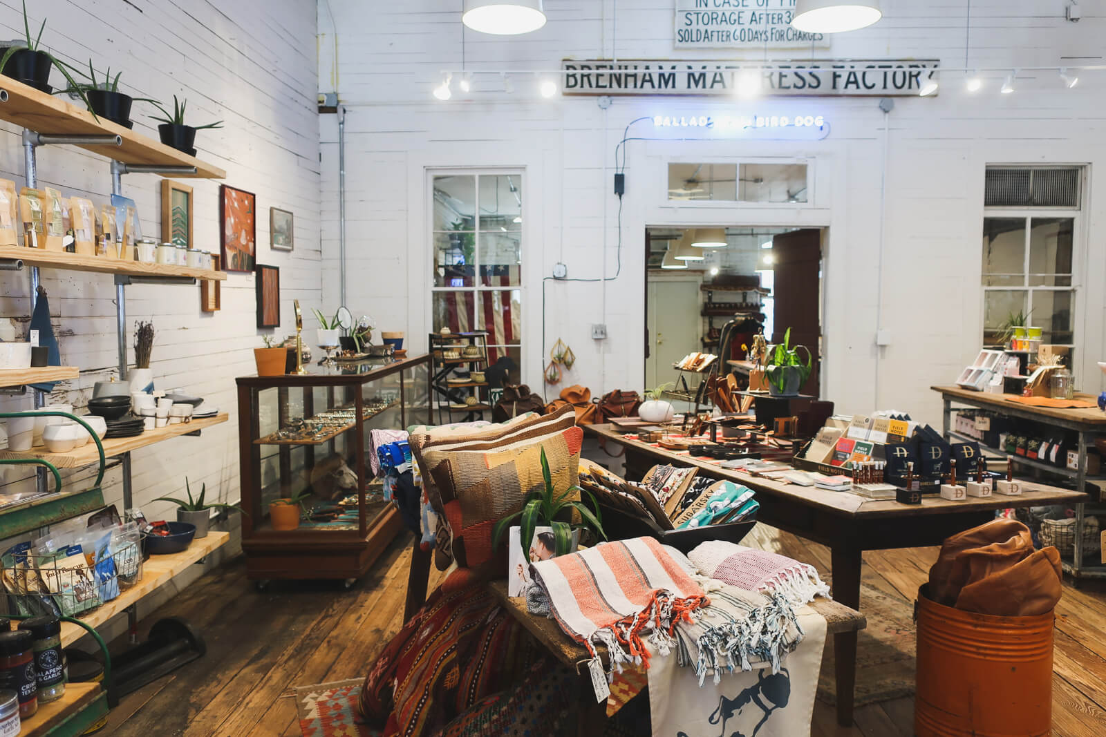 White washed rustic boards line a room of a store filled iwth antiques, jewelry and scarves in a small shop in Brenham Texas