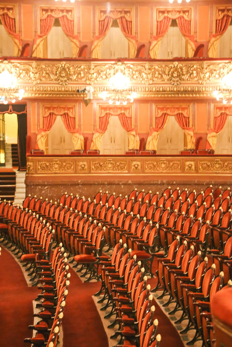 Rows of red velvet upholstered seats sit below gold leafed luxurious balconies in the Buenos Aires opera house